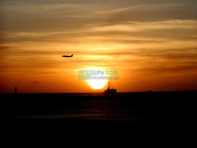 オレンジ色の空に飛ぶ飛行機・進む船(那覇エリアの壁紙/写真)