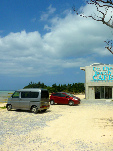 オンザビーチカフェの駐車場と外観と海