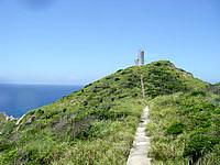 渡嘉敷島ウン島の阿波連岬灯台 - ウン島の南端にそびえ立っています
