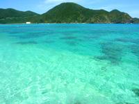 渡嘉敷島ハナレ島のハナレ島の海の色 - 遠くに見えるのが阿波連港の施設